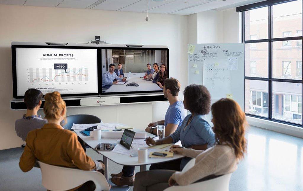5 Leute am Tisch die Video Zoom Konferenz mit Bildübertragung haben