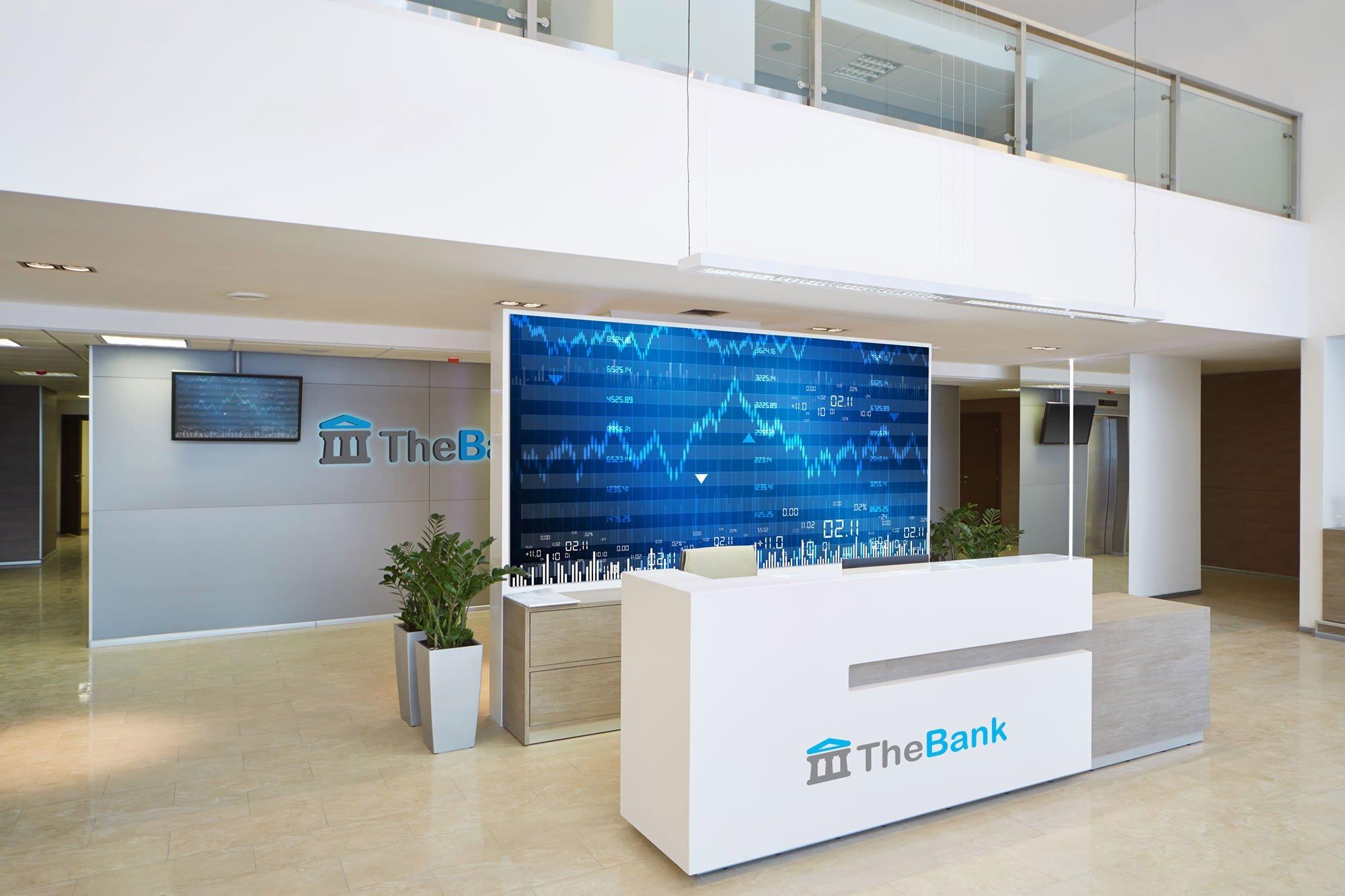 Eingangbereich einer Bank mit Rezeption und LED Wand im Hindergrund