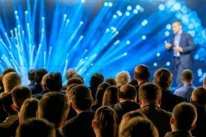 Bühne mit LED Wand mit Publikum davor und Präsentator